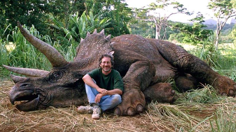 O diretor Steven Spielberg em frente a um animatronic de um Triceratops.